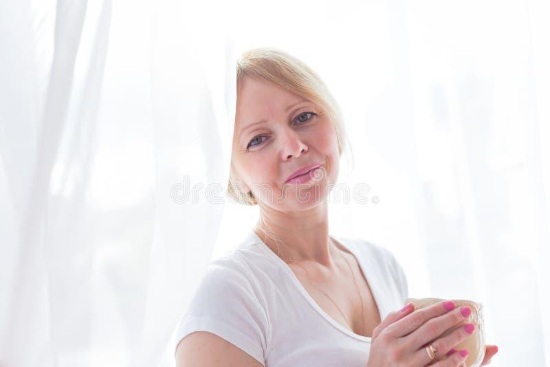 Um café bebendo da mulher superior ativa em casa imagem de stock royalty free