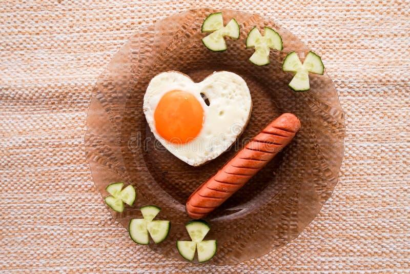 Um café da manhã adiantado dos ovos mexidos e das salsichas foto de stock royalty free