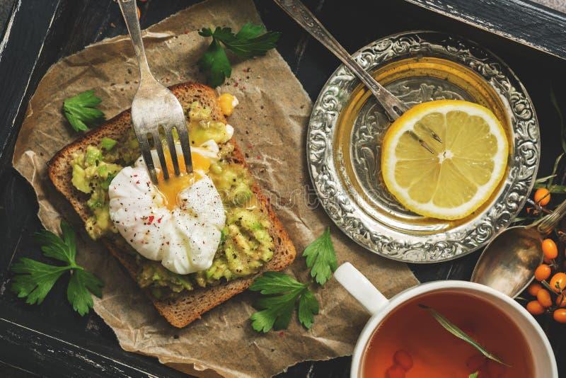 Um café da manhã fresco do ovo escalfado, do sanduíche do abacate e do chá do limão em uma bandeja rústica de madeira preta Vista imagens de stock