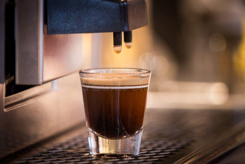 Um café fresco aromático espumoso que está sendo derramado da máquina do café em uma caneca de vidro fotografia de stock