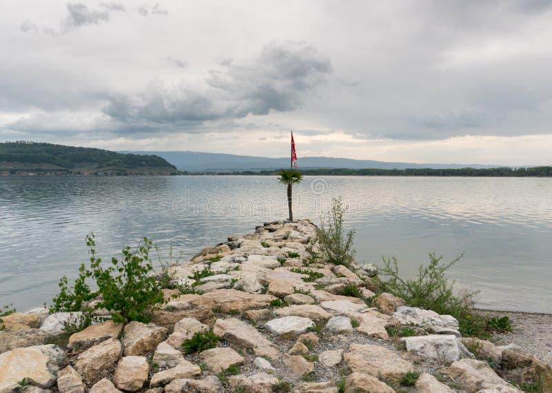 Um cais rochoso que conduz para fora em um lago calmo com um polo de bandeira e na bandeira na extremidade e em um beh bonito do  foto de stock royalty free