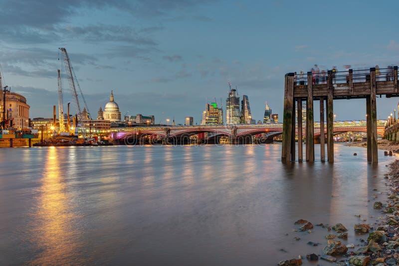 Um cais velho, a catedral do St Pauls, ponte de Blackfriars e a cidade de Londres imagens de stock