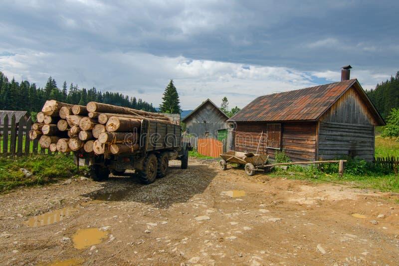 Um caminhão carregado com os logs e um carro em uma aldeia da montanha nos Carpathians ucranianos foto de stock royalty free
