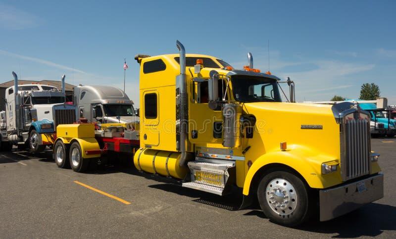 Um caminhão de reboque resistente usado transportando grandes equipamentos quebrados imagem de stock