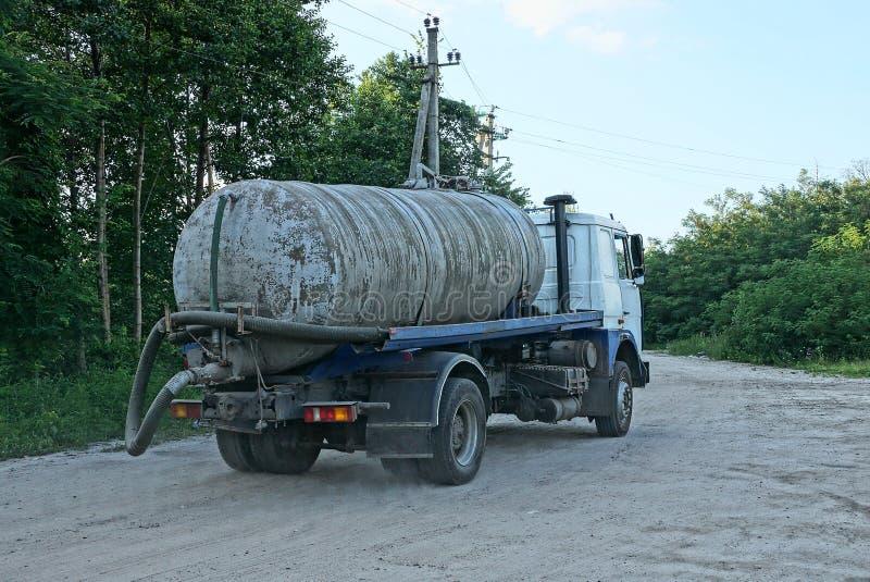 Um caminhão sujo grande com um tanque e uma mangueira para bombear para fora o cannonage da estrada fotografia de stock royalty free