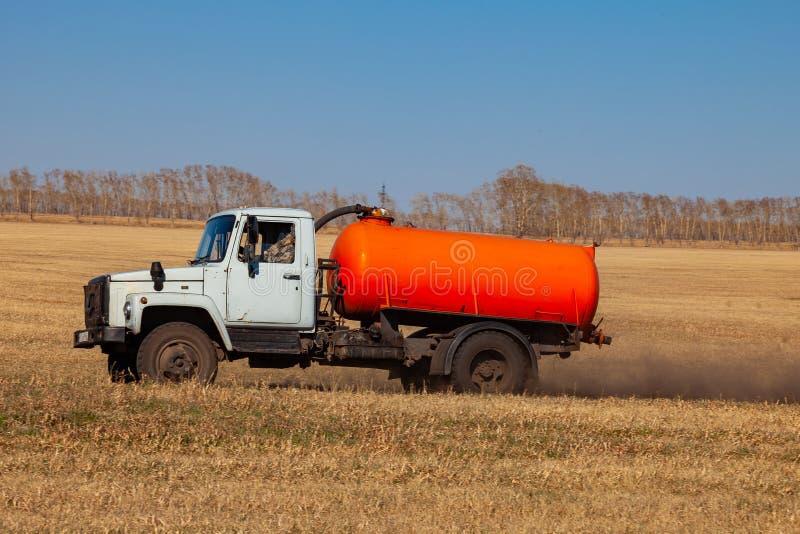 Um caminh?o para o transporte da gasolina e o combust?vel com um tanque alaranjado monta em um campo amarelo na estrada durante a fotos de stock