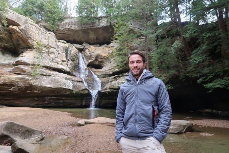 Um caminhante dos jovens levanta na frente de uma mini cachoeira imagem de stock