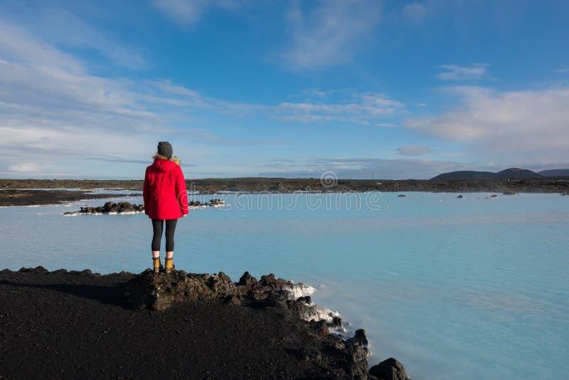 Um caminhante fêmea no stoping de Islândia para apreciar a vista de uma lagoa azul fotos de stock royalty free