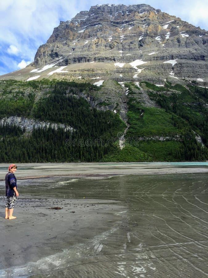 Um caminhante fêmea novo que anda com os pés descalços nos bancos molhados da areia do lago berg com a montanha da retaguarda no  foto de stock