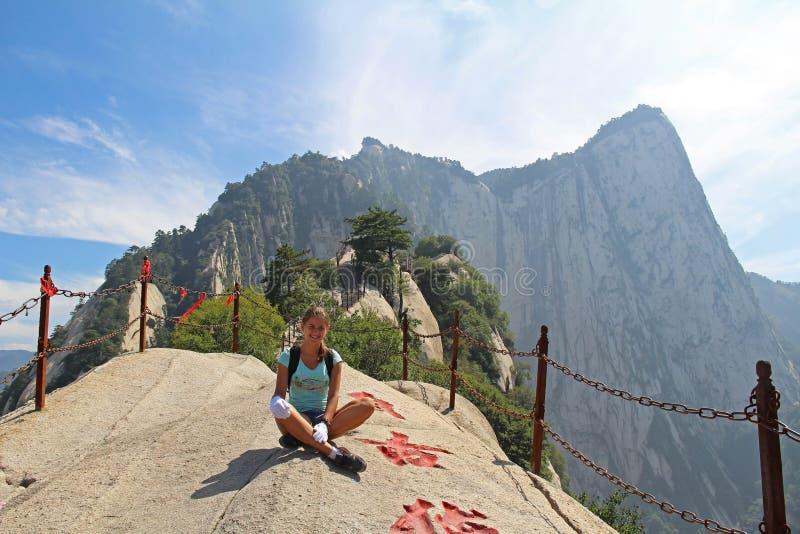 Um caminhante livre da moça está sentando-se no pico de montanha, montanha de Huashan, Xian, China fotografia de stock