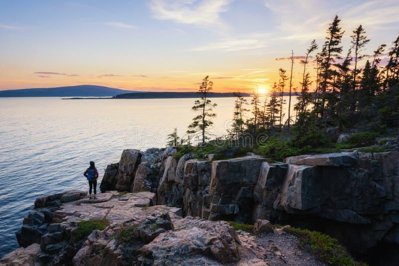Um caminhante que aprecia o por do sol no ponto Maine de Schoodic fotografia de stock