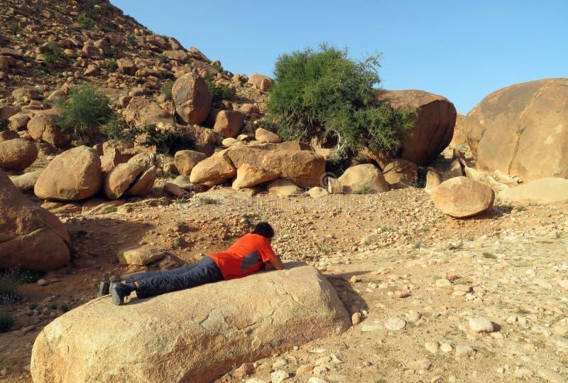 Um caminhante que toma uma ruptura nas montanhas de Marrocos, encontrando-se em uma pedra que olha seu smartphone imagem de stock