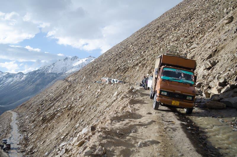 Um camionista dos bens que manobra seu veículo através de uma estrada estreita da montanha foto de stock royalty free