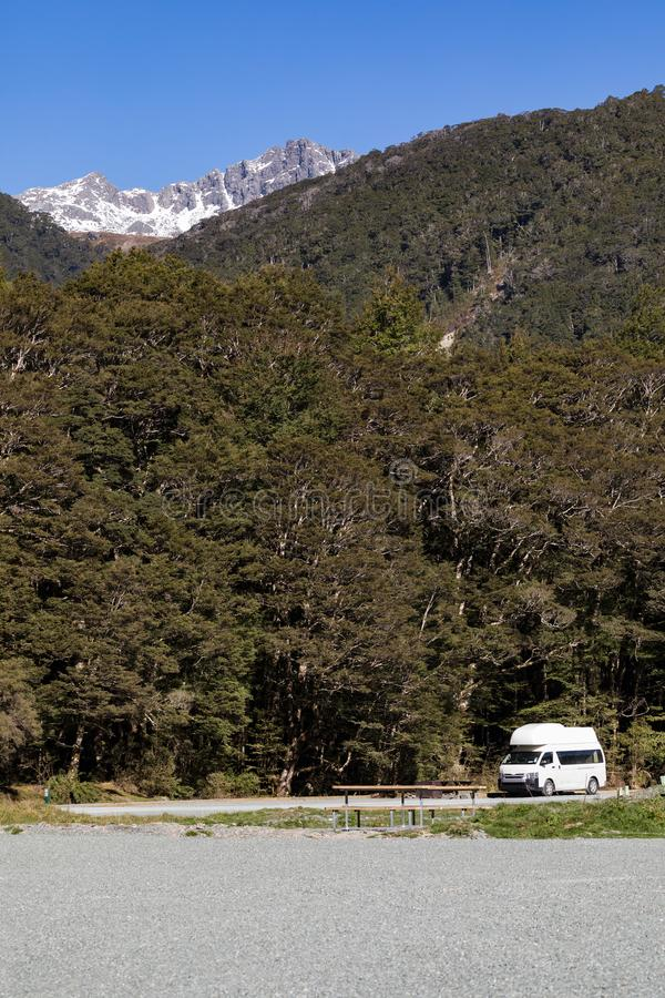 Um campervan contra a floresta e a neve tampou a montanha, acampamento da angra da cascata, parque nacional de Fiordland, Nova Ze fotografia de stock