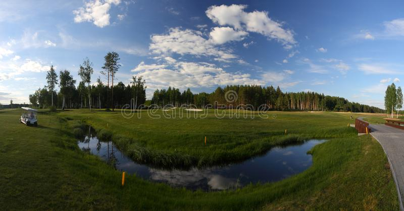 Um campo de golfe com estradas, depósitos e lagoas e com um rio imagens de stock