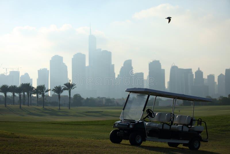 Um campo de golfe em Dubai com um pássaro, um golfcart e uns arranha-céus no fundo fotografia de stock royalty free