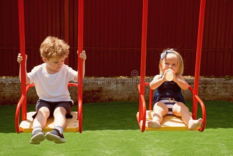 Um campo de jogos grande da aventura Estilos do corte de cabelo da menina e do menino Crianças pequenas com cabelo louro no balan imagens de stock royalty free