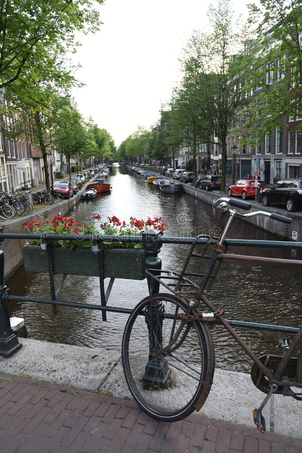 Um canal de Amsterdão alinhou com barcos e construções imagens de stock