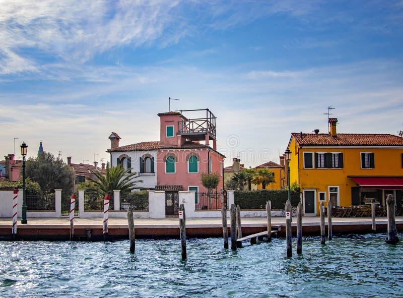 Um canal do mar com barcos no centro de Burano perto de Veneza em Itália fotografia de stock