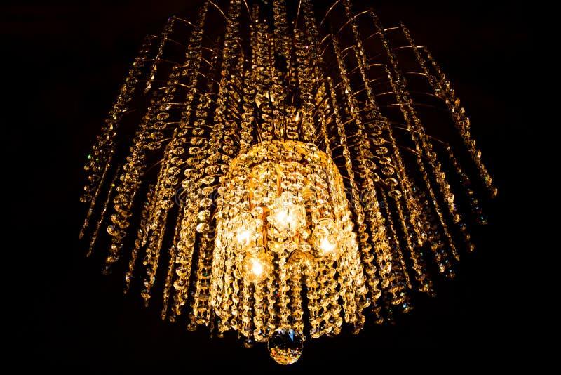 Um candelabro de cristal incandesce com luz dourada imagens de stock royalty free