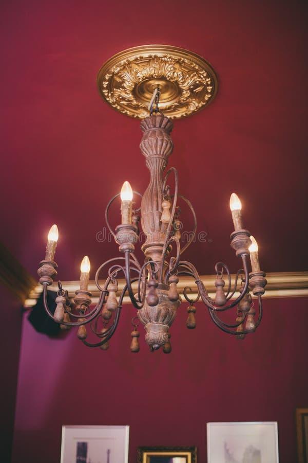 Um candelabro velho no teto, ampolas como velas Candelabro foto de stock royalty free