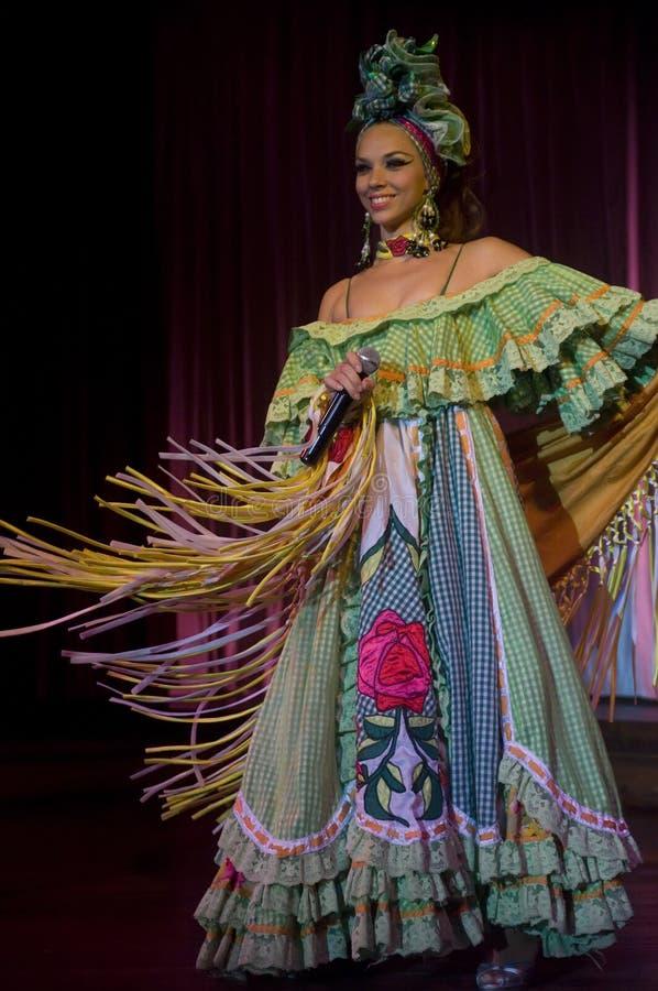 Um cantor fêmea cubano no vestuário tradicional durante o desempenho de Parisien da taberna