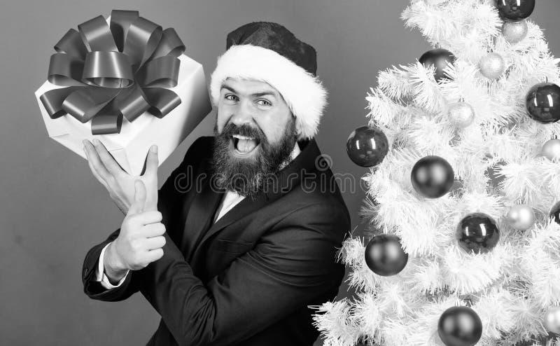 Um cara com uma caixa de presentes alegre com uma fita festiva Até adultos entusiasmados com tais presentes Espalhar alegria e fe imagens de stock royalty free