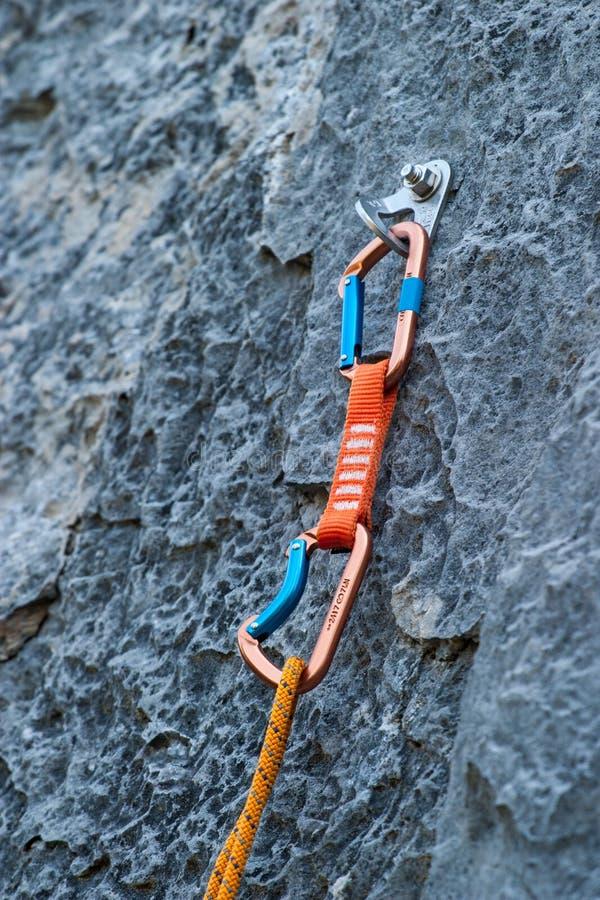 Um carabiner do quickdraw unido a um penhasco da rocha imagens de stock