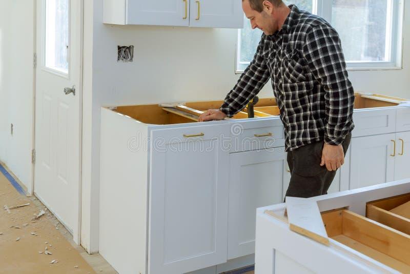 Um carpinteiro est? construindo um escaninho de lixo das gavetas na cozinha imagem de stock