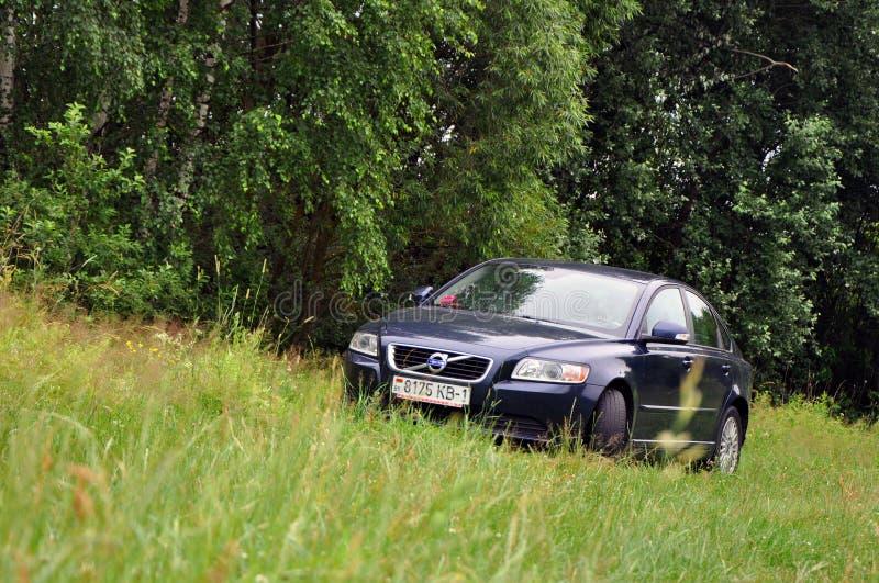 Um carro é estacionado na grama fora da cidade fotografia de stock