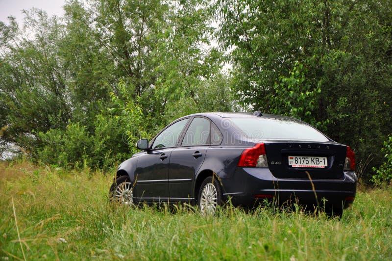Um carro é estacionado na grama fora da cidade imagens de stock royalty free