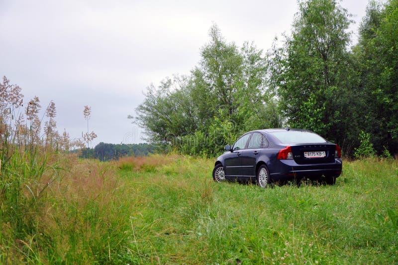 Um carro é estacionado na grama fora da cidade imagem de stock royalty free