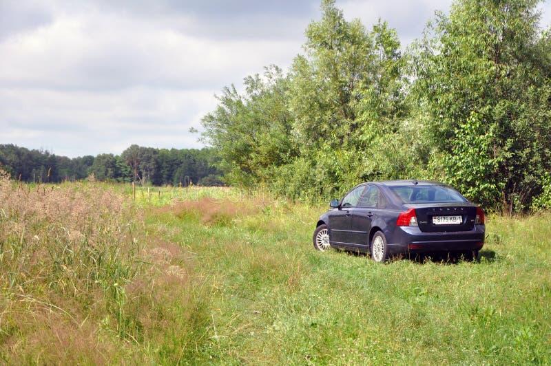 Um carro é estacionado na grama fora da cidade foto de stock