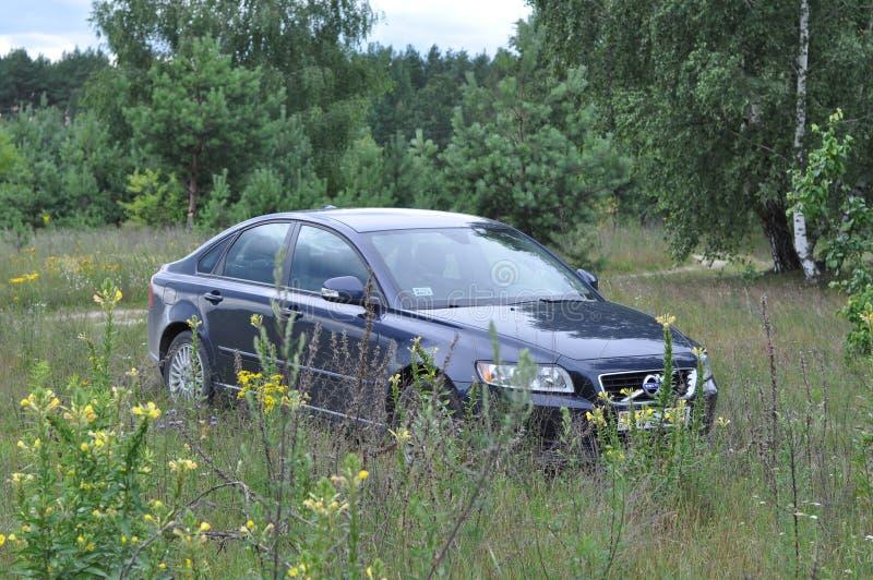 Um carro é estacionado na grama fora da cidade fotografia de stock royalty free
