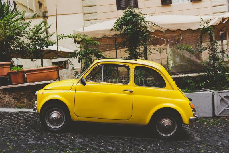 Um carro amarelo em uma rua pequena em Roma fotografia de stock royalty free