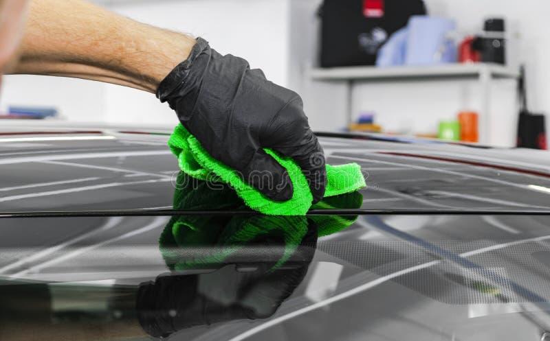 Um carro da limpeza do homem com pano do microfiber Conceito de detalhe do carro Detalhe do carro Limpeza com a esponja Limpeza d fotos de stock royalty free