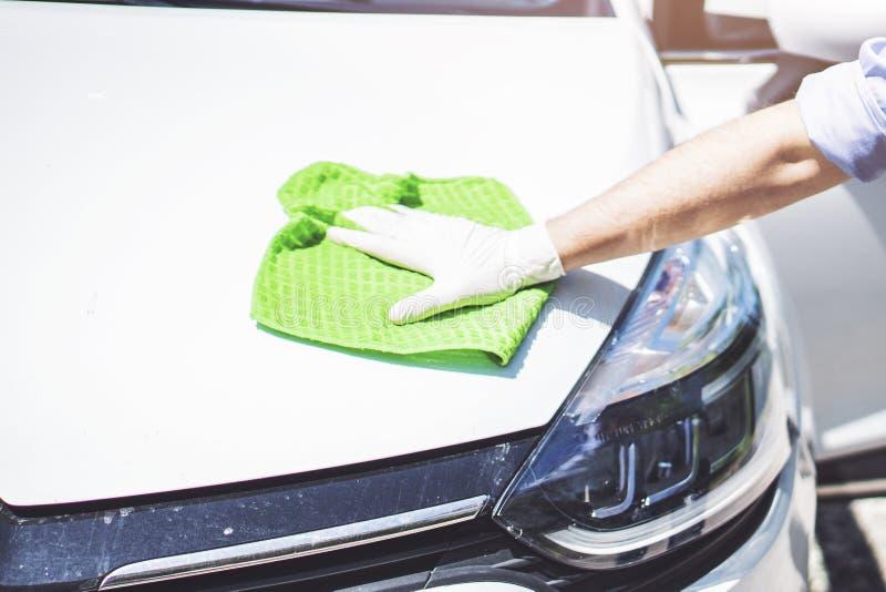 Um carro da limpeza do homem com pano do microfiber, conceito de detalhe ou valeting do carro Foco seletivo fotografia de stock royalty free