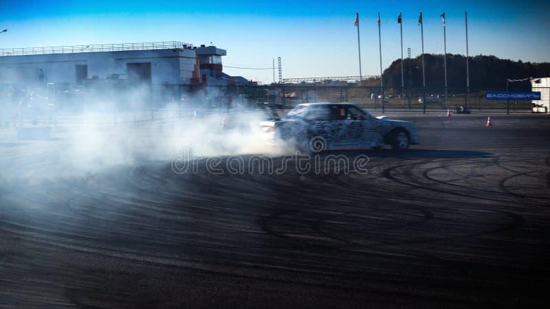 Um carro de competência da tração na ação com os pneus de fumo na mostra fotos de stock