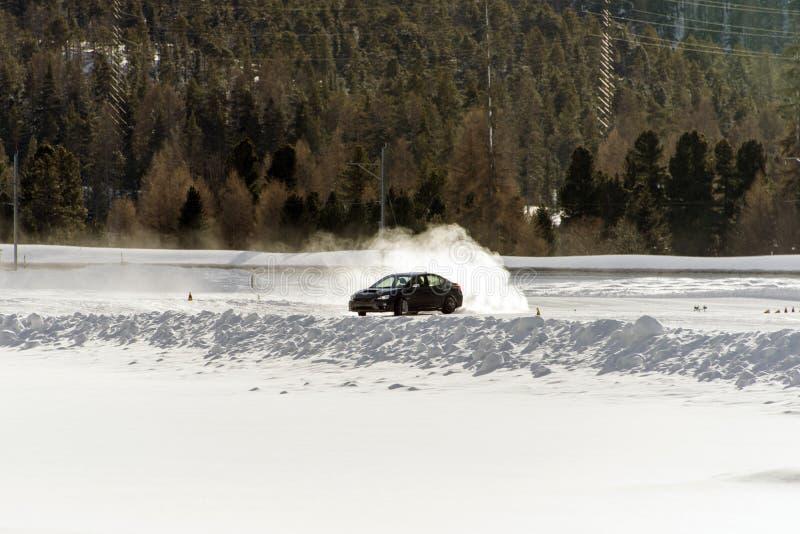 Um carro de esportes no gelo que apressa-se e que queima-se cansa-se no inverno em uma pista nevado do gelo imagem de stock