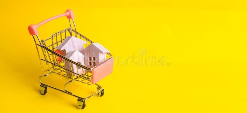 Um carro do supermercado com casas de madeira está em um fundo amarelo O conceito das compras ao domicílio e o mercado, o comérci fotografia de stock royalty free