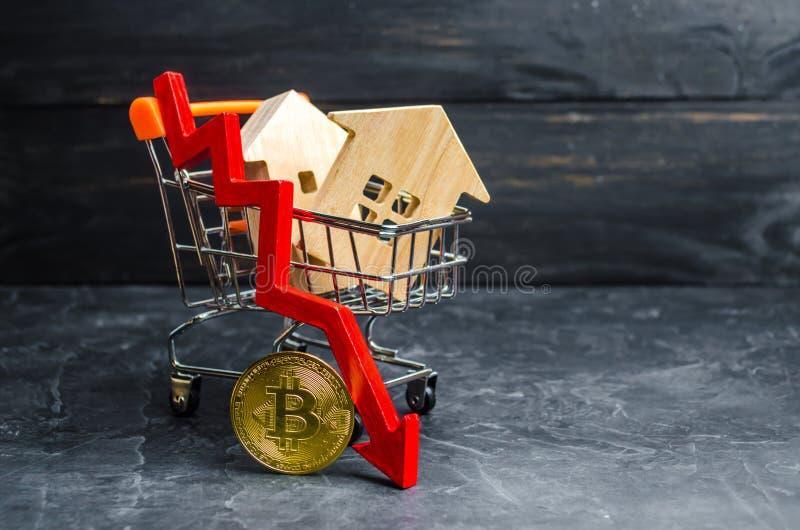 Um carro do supermercado com casas e bitcoin e uma seta vermelha da pena valor de queda Bitcoin e a insegurança do investme a lon fotografia de stock