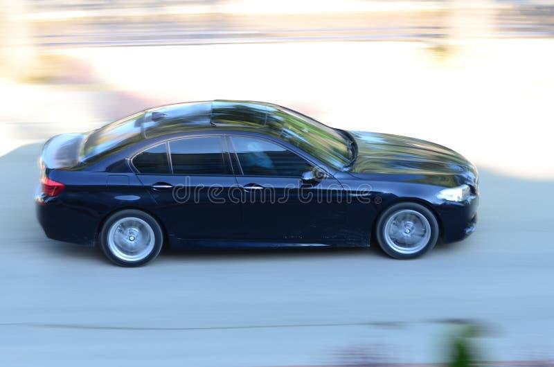 Um carro dos azuis marinhos que passa através da estrada fotografia de stock