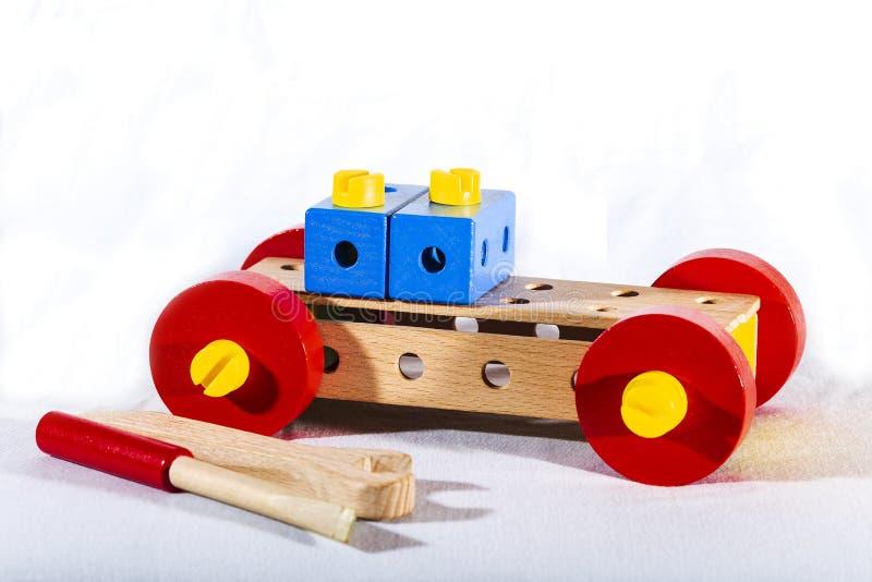 Um carro feito pelas mãos de uma criança das partes de um construtor de madeira foto de stock