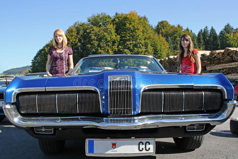 Um carro velho e duas meninas do joung foto de stock royalty free