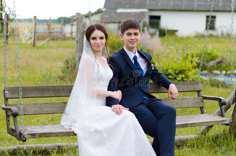 Um casal bonito nos vestidos de casamento, levantando para um tiro da foto em uma vila bielorrussa Fundo verde fotografia de stock
