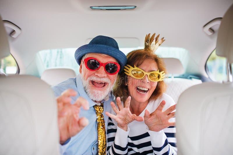 Um casal feliz com acessórios de festa sentados no carro, divertindo-se imagens de stock royalty free