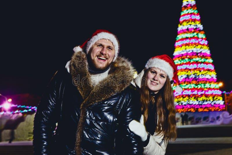 Um casal feliz de sorriso novo no tampão vermelho no Natal fora imagem de stock