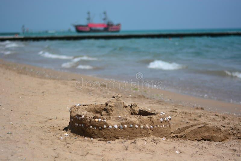 Um castelo na areia com escudos foto de stock royalty free