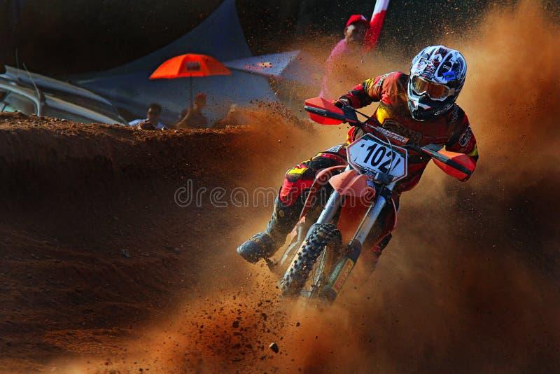 um cavaleiro áspero da motocicleta está tomando uma volta afiada no competiam do motocross fotografia de stock royalty free