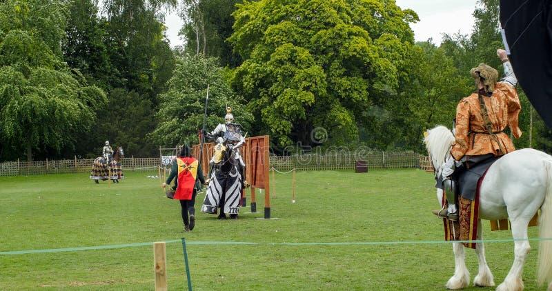 Um cavaleiro e um cavalo medievais na armadura e no traje prontos para jousting foto de stock